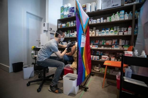 Pharmacist Eugene Woo delivers an AstraZeneca COVID-19 vaccine to a person at Davie Pharmacy in Vancouver on April 20.