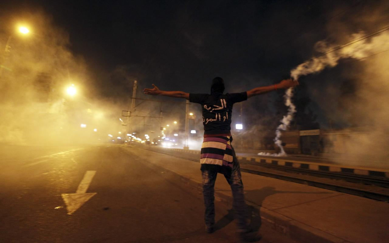 A protester shouts at police as smoke rises around him (Reuters)