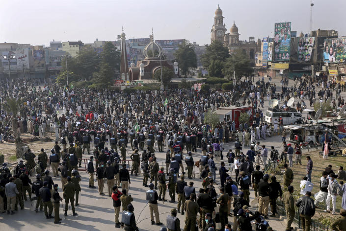 Pakistani police officers stand guard while supporters of the Pakistan Democratic Movement, an alliance of opposition parties, gather at a main intersection before an anti-government rally, in Multan, Pakistan, Monday, Nov. 30, 2020. Pakistani police arrested hundreds of supporters of opposition parties ahead of a planned rally Monday calling for the country's prime minister to resign, a move the government defended as necessary to combat the coronavirus pandemic. (AP Photo/Asim Tanveer)