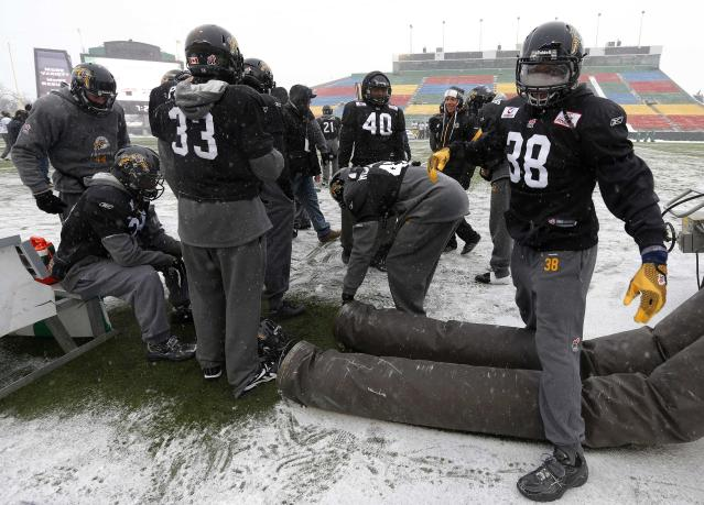 Players from the Hamilton Tiger-Cats try and warm up in the extreme cold during the team practice in Regina, Saskatchewan, November 20, 2013. The Saskatchewan Roughriders will play the Hamilton Tiger-Cats in the CFL's 101st Grey Cup in Regina November 24. REUTERS/Todd Korol (CANADA - Tags: SPORT FOOTBALL)