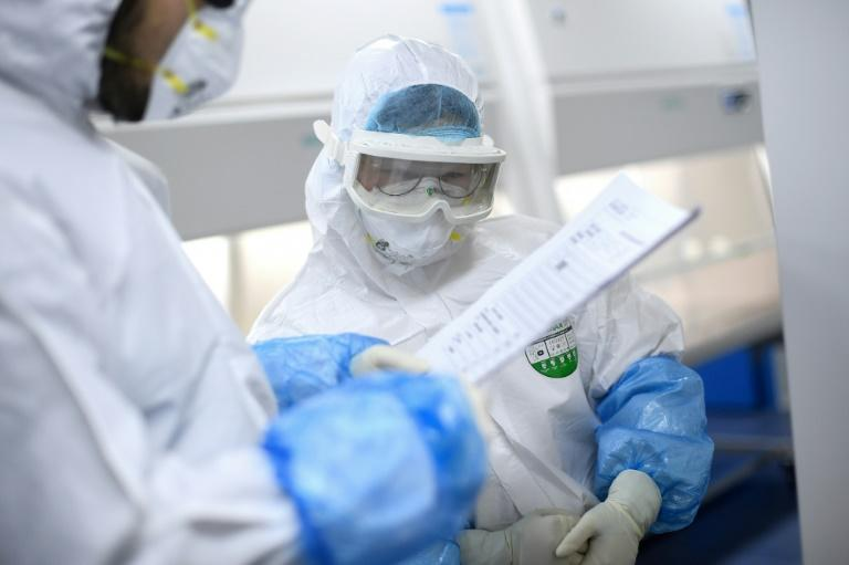 A lab technician works on samples being tested in Wuhan