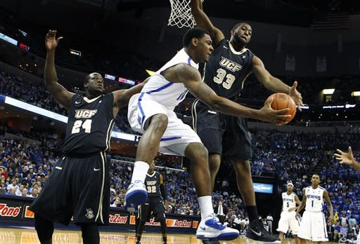 Memphis' Tarik Black, middle, looks to pass around UCF's Keith Clanton, right, and Josh Crittle, left, during first half action of an NCAA college basketball game at the FedExForum Tuesday Feb. 28, 2012. (AP Photo/The Commercial Appeal, Mark Weber)