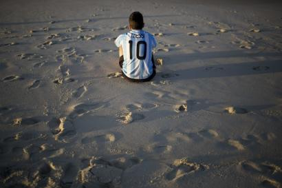 An Argentina soccer fan, wearing a Lionel Messi soccer jersey, sits on Copacabana beach the morning after his team was defeated by Germany at the World Cup final, in Rio de Janeiro, Brazil, Monday, July 14, 2014. (AP Photo/Rodrigo Abd)