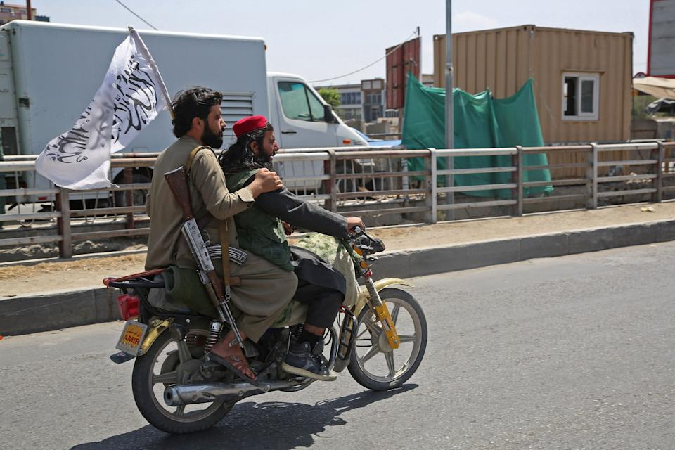 Taliban fighters ride a motorbike along the street in Kabul on August 16, 2021, after a stunningly swift end to Afghanistan's 20-year war, as thousands of people mobbed the city's airport trying to flee the group's feared hard-line brand of Islamist rule. (-/AFP via Getty Images)