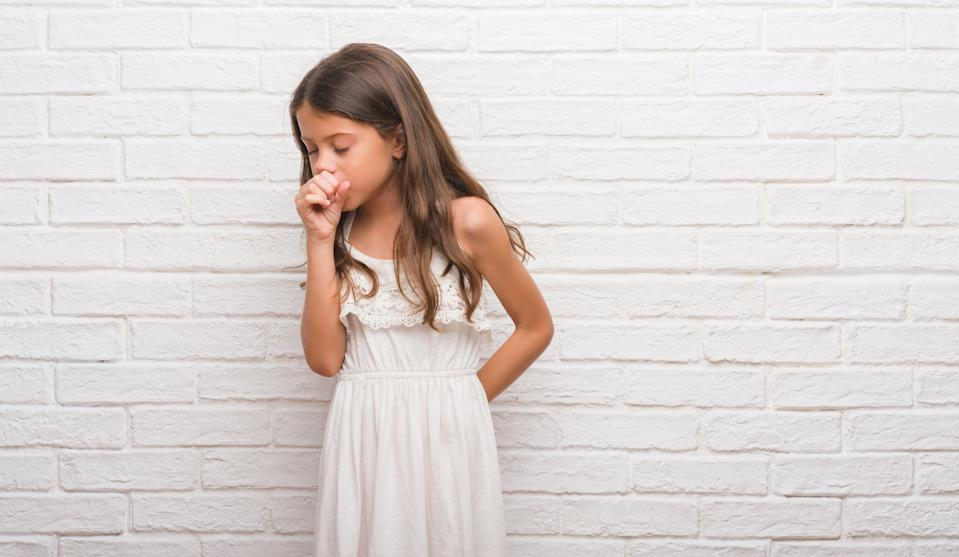 Young hispanic kid over white brick wall feeling unwell and coughing as symptom for cold or bronchitis. Healthcare concept.