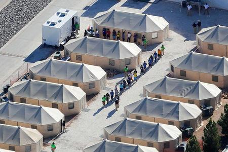 """FILE PHOTO:   Immigrant children now housed in a tent encampment under the new """"zero tolerance"""" policy by the Trump administration are shown walking in single file at the facility near the Mexican border in Tornillo, Texas, U.S. June 19, 2018.        REUTERS/Mike Blake/File Photo"""