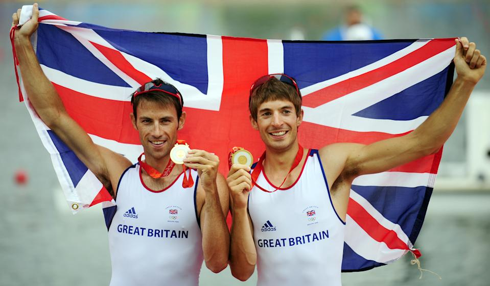 Britain's Zac Purchase and Mark Hunter celebrate on the podium during the medals ceremony for the lightweight men's double sculls at the Shunyi Rowing and Canoeing Park in Beijing  on August 17, 2008.  Britain won gold, Greece silver and Denmark bronze.   AFP PHOTO / FRED DUFOUR (Photo by Fred DUFOUR / AFP) (Photo by FRED DUFOUR/AFP via Getty Images)