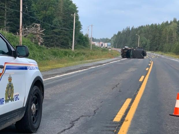 A vehicle is seen turned on its side on Highway 105 in Cape Breton on Saturday. (Brittany Wentzell/CBC - image credit)