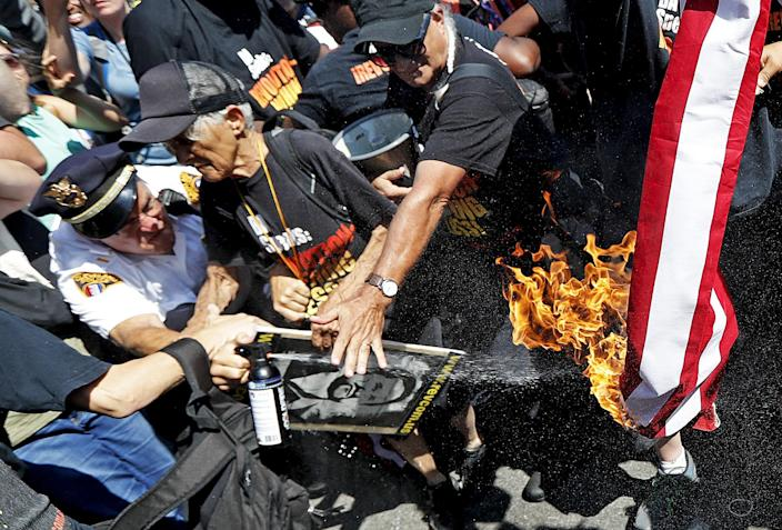 A law enforcement officer tries to extinguish a burning American flag on July 20, 2016, in Cleveland, Ohio, during the third day of the RNC. (Photo: John Minchillo/AP)