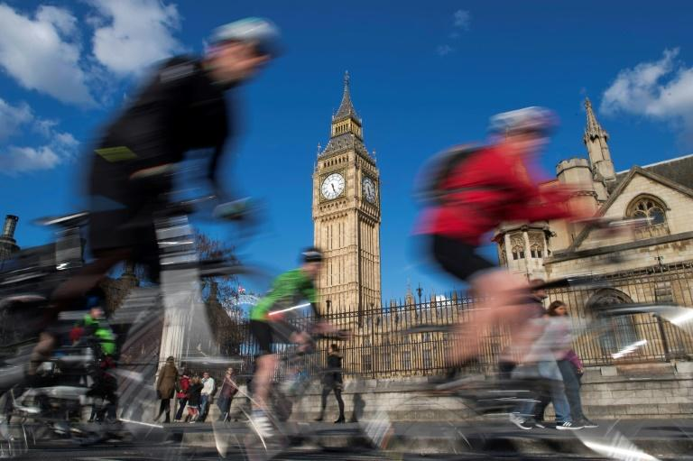 Cyclists ride past the clock face of the Elizabeth Tower, commonly referred to as Big Ben, at the Houses of Parliament in London on April 18, 2017. Parliament votes Wednesday on holding a snap election in June