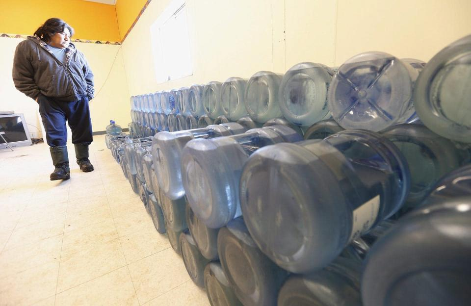 An Indigenous man surveys a collection of large water jugs.