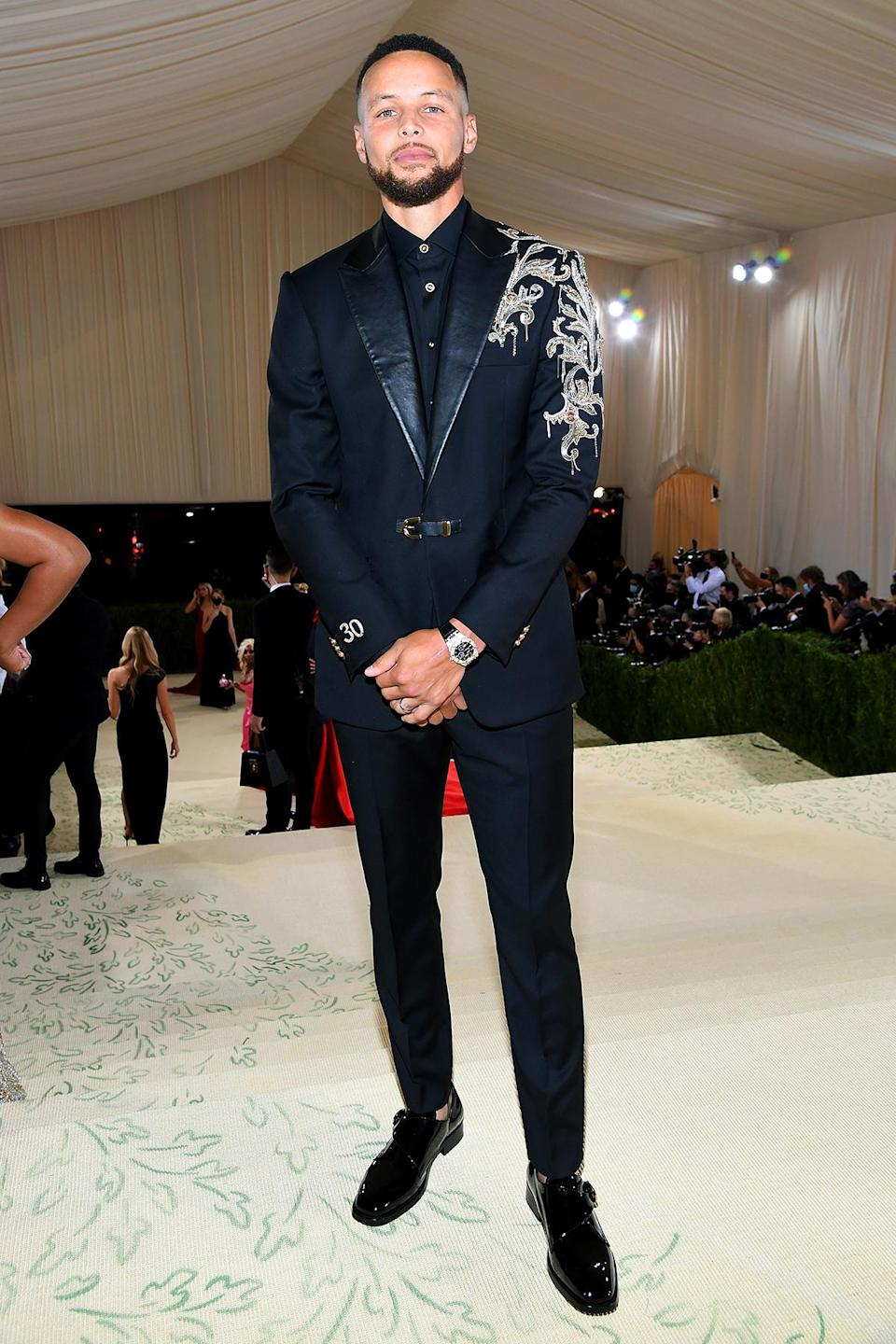 <p>Pausing for a solo photo without his wife Ayesha Curry, the NBA player looked dapper in his embroidered custom suit by Versace.</p>