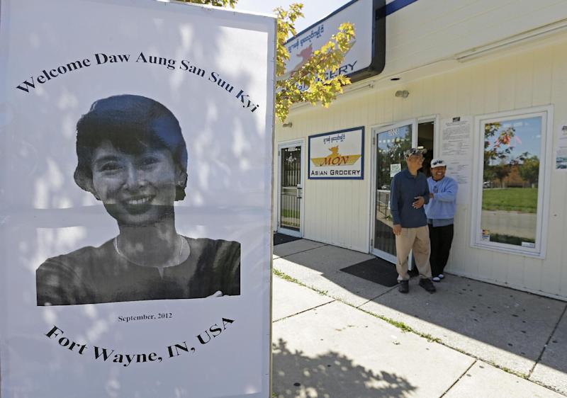 In this Thursday, Sept. 20, 2012 photo, Nai Sike and Paung Pakong, right, walk out of Sike's grocery store, where a display of Myanmar democracy leader Aung San Suu Kyi is displayed in front, in Fort Wayne, Ind. The city of 256,000, home to one of the nation's largest Burmese populations, has become an unlikely base for opposition to the former Burma's military regime. (AP Photo/Darron Cummings)