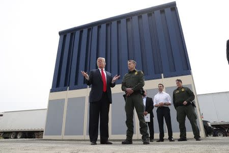 U.S. President Donald Trump talks with a U.S. Customs and Border Protection (CBP) Border Patrol Agent while participating in a tour of U.S.-Mexico border wall prototypes near the Otay Mesa Port of Entry in San Diego, California. U.S., March 13, 2018. REUTERS/Kevin Lamarque