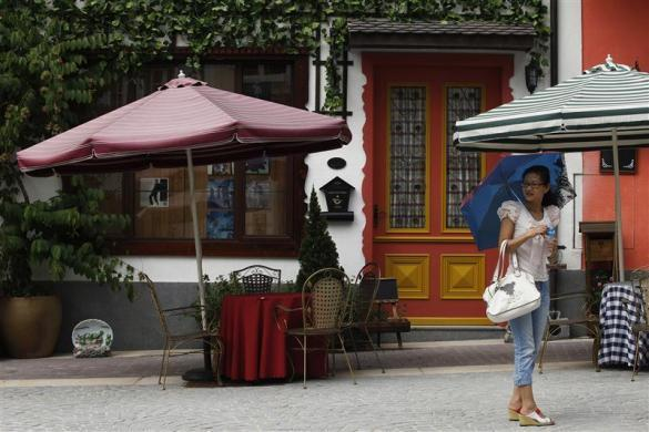 A woman is seen at the replica of Austria's UNESCO heritage site, Hallstatt village, in China's southern city of Huizhou in Guangdong province, June 1, 2012.