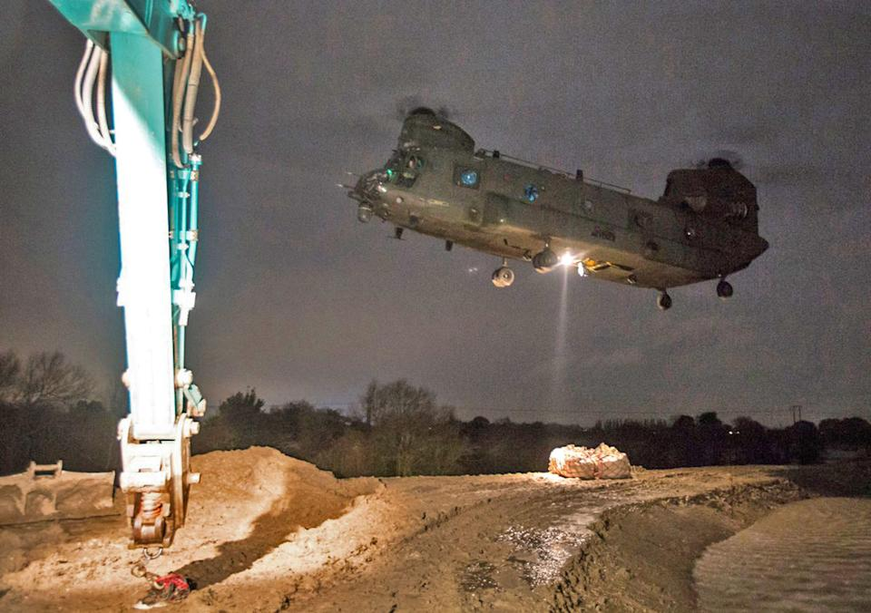 An RAF Chinook in Doncaster moving tonnes of aggregate to a cut off a spit of land to shore up flood defences (Picture: PA)