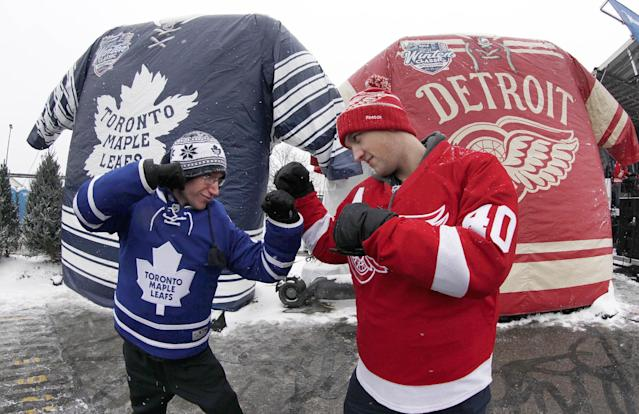 Nathan Dunville, of Halifax, Nova Scotia, left, and Adam Boutilier, of Cole Harbour, Nova Scotia, pose for family photographs at the NHL Winter Classic hockey game at Michigan Stadium in Ann Arbor, Mich., Wednesday, Jan, 1, 2014, where the Detroit Red Wings play the Toronto Maple Leafs. (AP Photo/Paul Sancya)