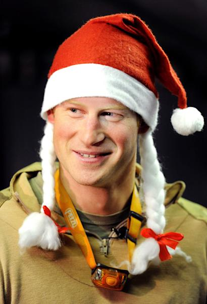 FILE - In this Dec. 12, 2012 file photo, Britain's Prince Harry wears a Santa hat as he shows a media crew his sleeping area at the VHR (very high readiness) tent, close to the flight-line, at Camp Bastion southern Afghanistan. During Prince Harry's 20-week deployment in Afghanistan, he served as an Apache helicopter pilot with the Army Air Corps. (AP Photo/ John Stillwell, Pool, File)