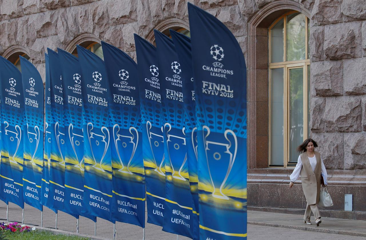 A woman walks past flags with the UEFA Champions League final logo in central Kiev, Ukraine May 21, 2018. REUTERS/Valentyn Ogirenko