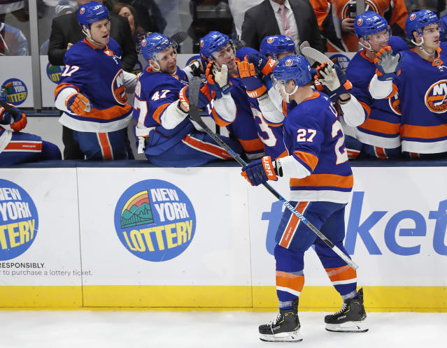 Teammates congratulate New York Islanders left wing Anders Lee (27) after Lee scored a goal against the Colorado Avalanche during the third period of an NHL hockey game, Monday, Jan. 6, 2020, in Uniondale, N.Y. The Islanders defeated the Avalanche 1-0 on Lee's goal. (AP Photo/Kathy Willens)
