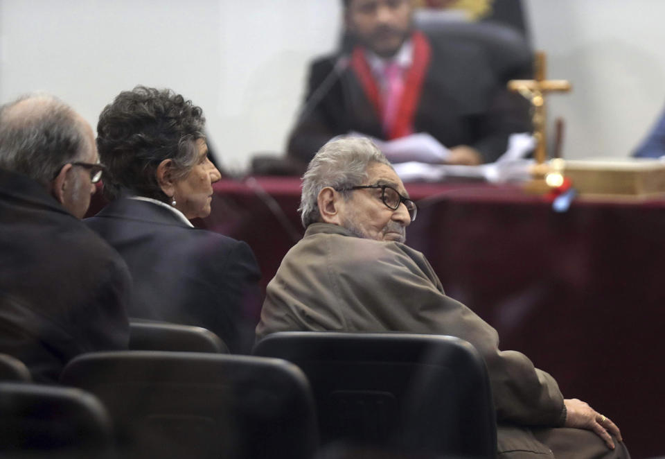 FILE - In this Sept. 11, 2018 file photo taken through a window, Abimael Guzman, founder and leader of the Shining Path guerrilla movement, looks at his lawyer while siting with his partner Elena Iparraguirre, during the sentencing phase of their trial at a naval base in Callao, Peru. The Peruvian government reported Saturday, Sept. 11, 2021, that Guzman died after an illness. (AP Photo/Martin Mejia, File)