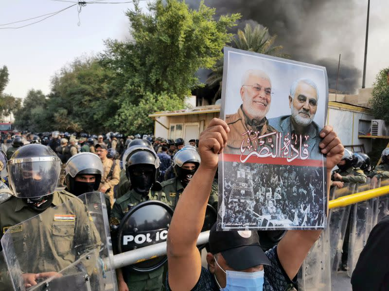 FILE PHOTO: A supporter of Hashid Shaabi (Popular Mobilization Forces) holds a picture of late Iran's Quds Force top commander Qassem Soleimani and Iraqi militia commander Abu Mahdi al-Muhandis who were killed in a U.S. airstrike during a protest in Baghda