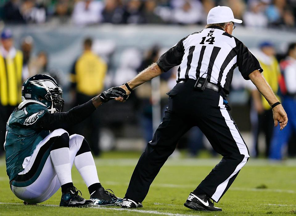 PHILADELPHIA, PA - SEPTEMBER 30: Referee Ron Winter helps quarterback Michael Vick #7 of the Philadelphia Eagles up after being tackled against the New York Giants at Lincoln Financial Field on September 30, 2012 in Philadelphia, Pennsylvania. (Photo by Rob Carr/Getty Images)