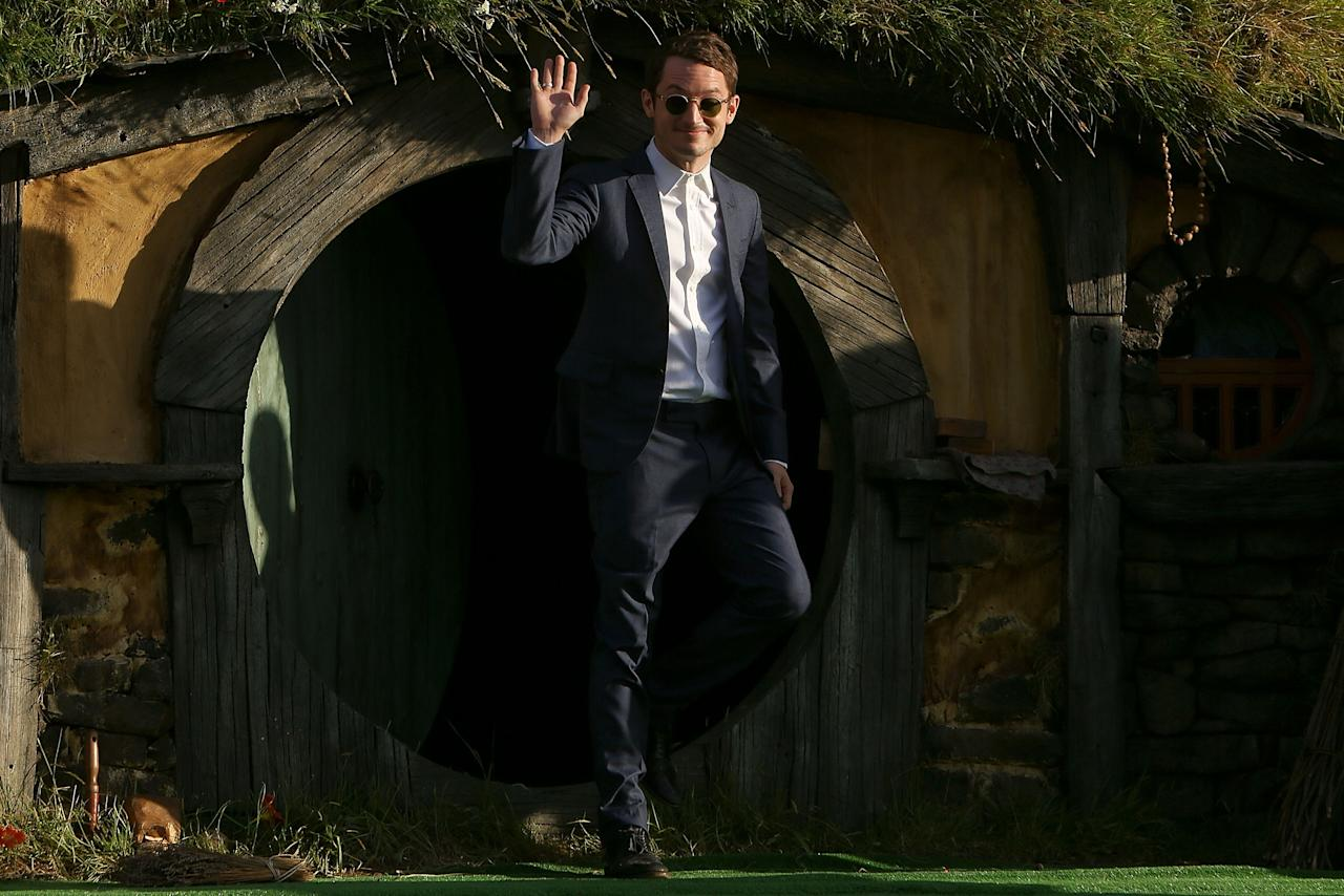 """WELLINGTON, NEW ZEALAND - NOVEMBER 28:  Elijah Wood emerges from from a Hobbit house at the """"The Hobbit: An Unexpected Journey"""" World Premiere at Embassy Theatre on November 28, 2012 in Wellington, New Zealand.  (Photo by Hagen Hopkins/Getty Images)"""