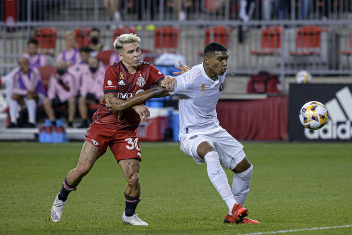 Toronto FC midfielder Yeferson Soteldo (30) is shielded from the ball by IInter Miami defender Christian Makoun during the first half of an MLS soccer match Tuesday, Sept. 14, 2021, in Toronto. (Christopher Katsarov/The Canadian Press via AP)