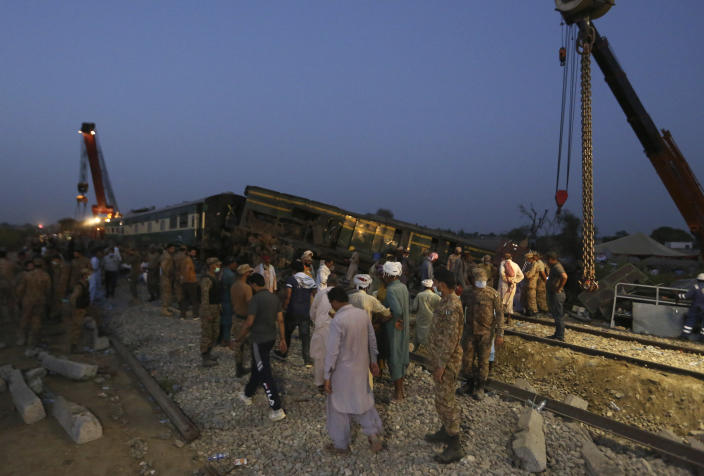 Soldiers and railway workers conduct a rescue operation to clear the track at the site of a train collision in the Ghotki district, southern Pakistan, Monday, June 7, 2021. An express train barreled into another that had derailed in Pakistan before dawn Monday, killing dozens of passengers, authorities said. More than 100 were injured, and rescuers and villagers worked throughout the day to search crumpled cars for survivors and the dead. (AP Photo/Fareed Khan)