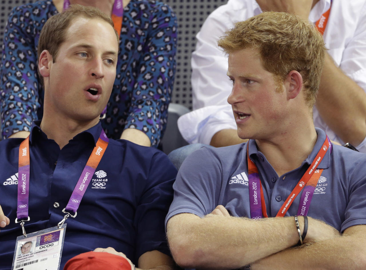 Britain's Prince William, left, and Prince Harry talk while watching track cycling at the velodrome during the 2012 Summer Olympics, Thursday, Aug. 2, 2012, in London. (AP Photo/Matt Rourke)