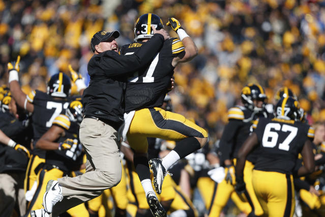"""FILE - In this Oct. 26, 2013, file photo, Iowa strength and conditioning coach Chris Doyle, front left, celebrates with defensive back John Lowdermilk (37) following their win in overtime against Northwestern in an NCAA college football game in Iowa City, Iowa. Iowa football strength and conditioning coach Doyle has been placed on administrative leave after several black former players posted on social media about what they described as systemic racism in the program. Head coach Kirk Ferentz made the announcement Saturday, June 6, 2020, calling it """"a defining moment for Iowa's football program in a video posted on the team's Twitter account. (AP Photo/Brian Ray, File )"""