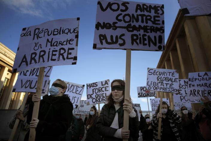Demonstrators chant slogans during a protest against bill on police images, in Paris, Saturday, Nov. 21, 2020. Thousands of people took to the streets in Paris and other French cities Saturday to protest a proposed security law they say would impinge on freedom of information and media rights. The board reads: Your guns against our cameras. (AP Photo/Christophe Ena)