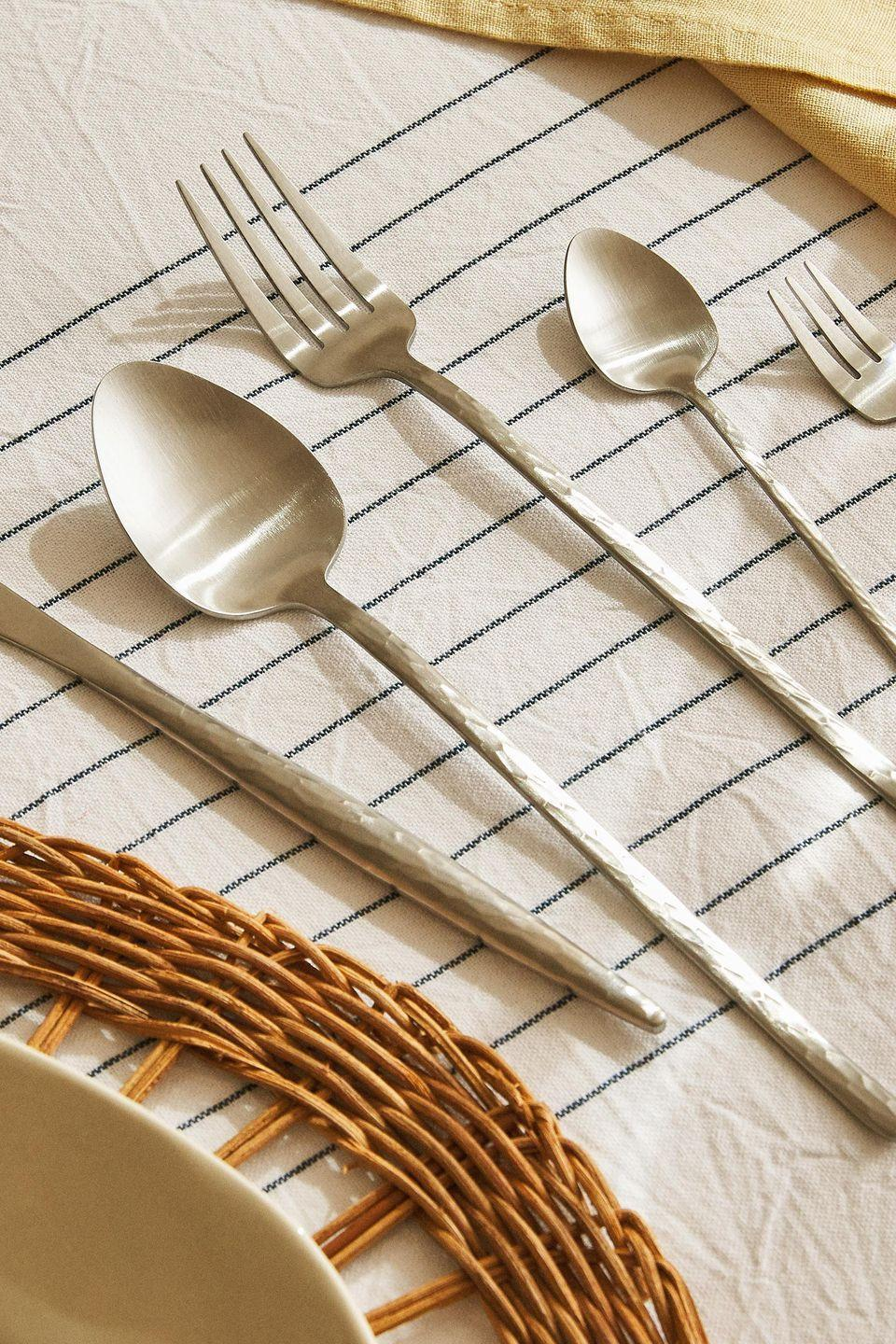 """<p>Add a tactile quality to meal times with Zara's subtly textured stainless steel cutlery. Its gently hammered surface, matt finish and elegant handle shape will ensure your table settings always look Instagram-ready. From £17.99 for a set of four dessert spoons, <a href=""""https://www.zarahome.com/gb/"""" rel=""""nofollow noopener"""" target=""""_blank"""" data-ylk=""""slk:zarahome.com"""" class=""""link rapid-noclick-resp"""">zarahome.com</a></p>"""