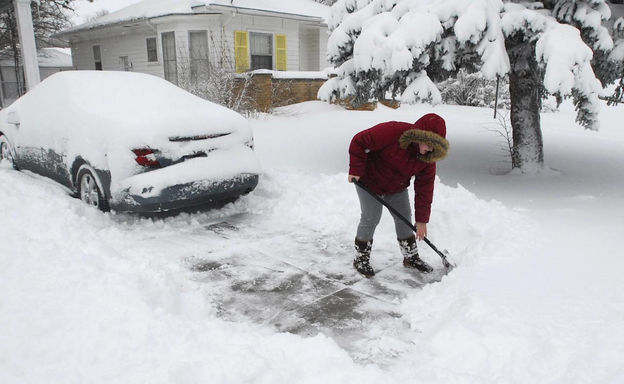Mackenzie Nix clears the snow from her driveway on Tuesday, Dec. 20, 2011, in Hays, Kansas, after a winter storm dumped up to 10 inches of snow as it moved northeastward Monday out of New Mexico. (AP Photo/The Hays Daily News, Steven Hausler)