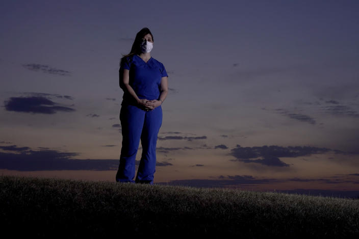 Emergency room nurse L'Erin Ogle stands at dawn before starting her 12-hour shift at a nearby hospital Tuesday, March 9, 2021, in Overland Park, Kan. After a year of working long hours taking care of COVID-19 patients, Ogle feels obligated to speak out when she sees misinformation related to the pandemic in her community. (AP Photo/Charlie Riedel)