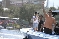 FILE - Tampa Bay Buccaneers NFL football quarterback Tom Brady waves to fans as he celebrates their Super Bowl 55 victory over the Kansas City Chiefs with a boat parade in Tampa, Fla., in this Wednesday, Feb. 10, 2021, file photo. Viewership in the Boston market topped that of the Tampa, Fla. market for last season's Super Bowl, and New England fans continue to tune in for Brady's games in droves through the first two weeks of this season. (AP Photo/Phelan Ebenhack, File)