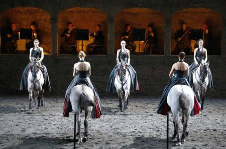 """Horses and riders perform on stage during a dress rehearsal of Wolfgang Amadeus Mozart's cantata """"Davide penitente"""" in Salzburg January 20, 2015.  REUTERS/Dominic Ebenbichler"""