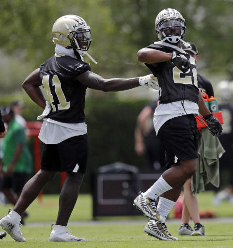 New Orleans Saints running back Mark Ingram II (22) dances to blasting music on the field as running back Alvin Kamara (41) touches his back during NFL football practice in Metairie, La., Tuesday, June 12, 2018. (AP Photo/Gerald Herbert)