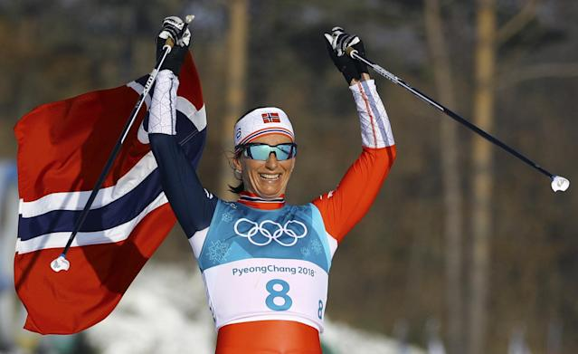 Cross-Country Skiing - Pyeongchang 2018 Winter Olympics - Women's 30km Mass Start Classic - Alpensia Cross-Country Skiing Centre - Pyeongchang, South Korea - February 25, 2018 - Gold medallist Marit Bjoergen of Norway celebrates victory with her national flag. REUTERS/Carlos Barria TPX IMAGES OF THE DAY
