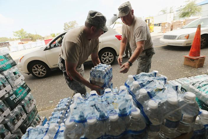 Louisiana Air National Guard soldiers distribute supplies to residents at a Point of Distribution center on September 3, 2012 in New Orleans, Louisiana. Around 240,000 residents remain without power in Louisiana following Hurricane Isaac. (Photo by Mario Tama/Getty Images)