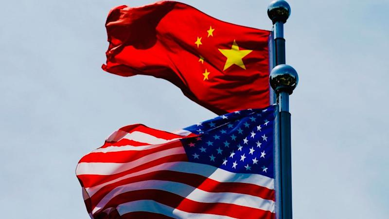 A Chinese flag and American flag wave in the wind.
