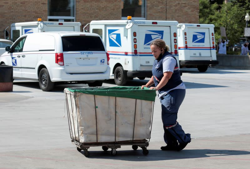 FILE PHOTO: A United States Postal Service (USPS) worker pushes a mail bin outside a post office in Royal Oak
