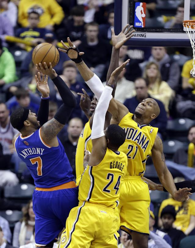 New York Knicks forward Carmelo Anthony, left, tries to shoot over Indiana Pacers' Paul George (24), David West (21) and Roy Hibbert during the second half of an NBA basketball game in Indianapolis, Thursday, Jan. 16, 2014. The Pacers defeated the Knicks 117-89. (AP Photo/Michael Conroy)