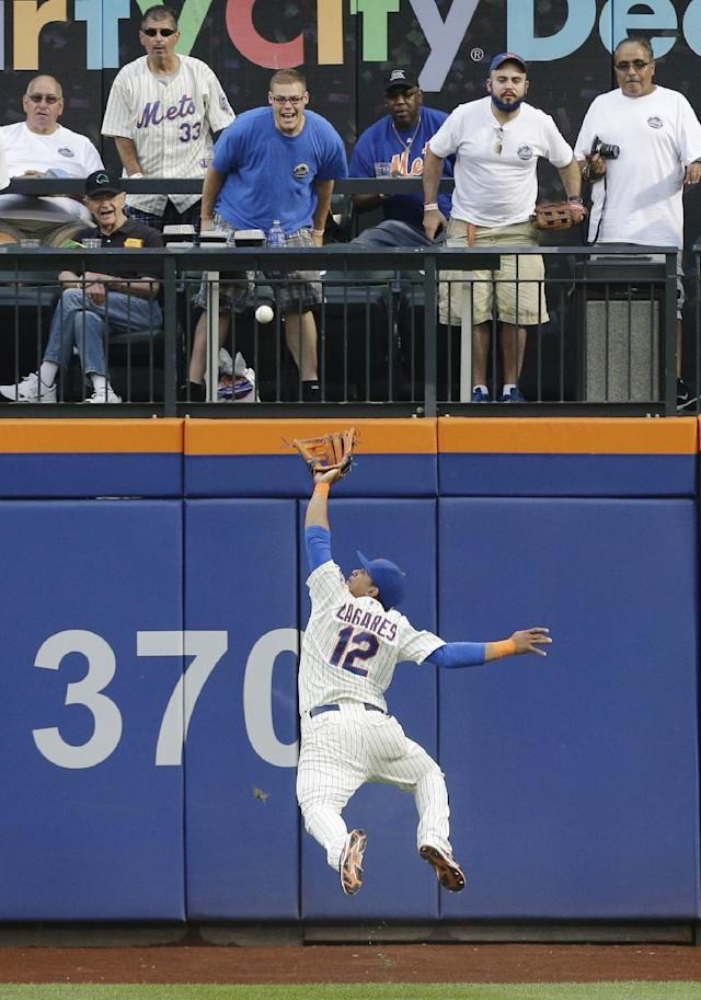 New York Mets center fielder Juan Lagares (12) jumps to catch a ball hit by San Francisco Giants' Brandon Belt for an out in the second inning of a baseball game Saturday, Aug. 2, 2014, in New York. (AP Photo/Frank Franklin II)