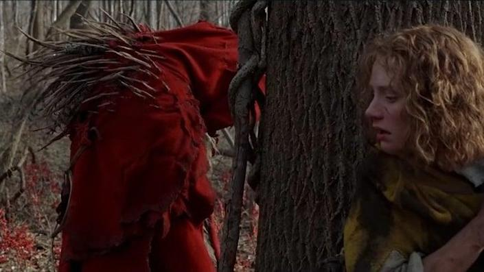 Bryce Dallas Howard hides behind a tree from a creature in a red cloak