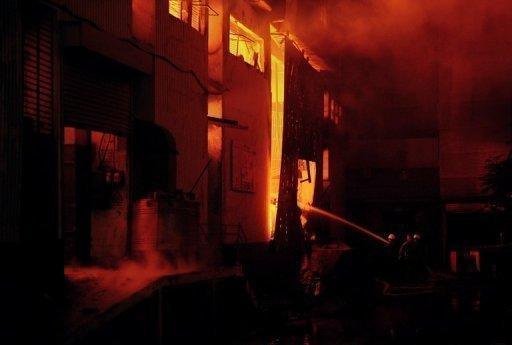 Pakistani firefighters battle a fire at a garment factory in Karachi September 11. Shouting and sobbing relatives of trapped workers, desperate to get inside the factory, scuffled with police overnight as rescuers battled to work through the night, an AFP photographer said