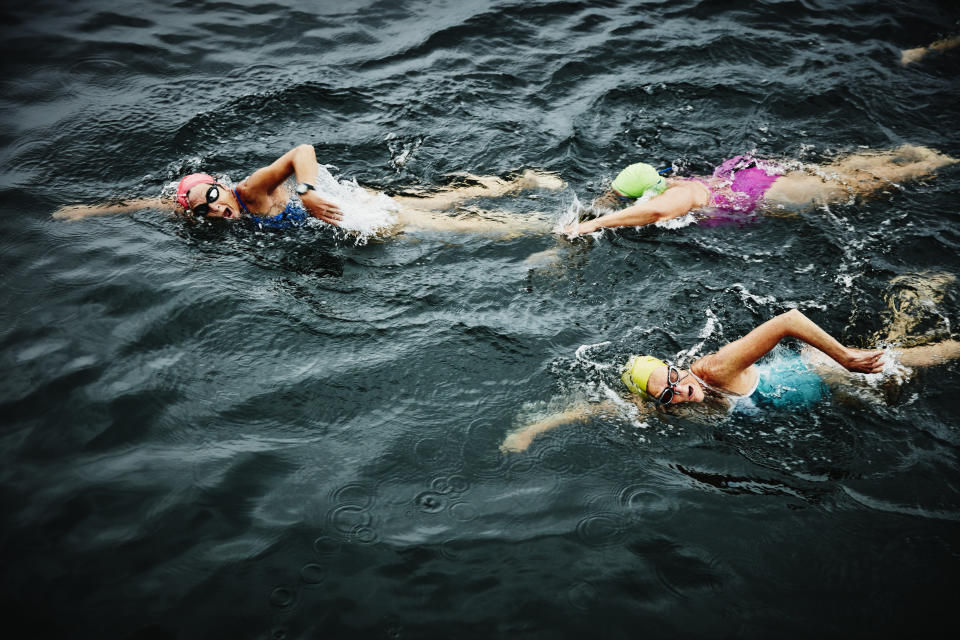 Mature female swimmers on early morning open water swim