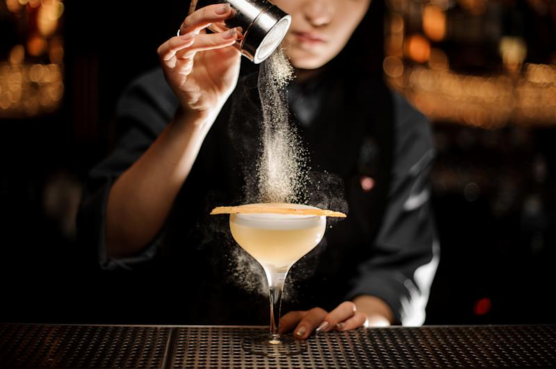 Female bartender pours an alcohol light brown cocktail with sour mix in glass
