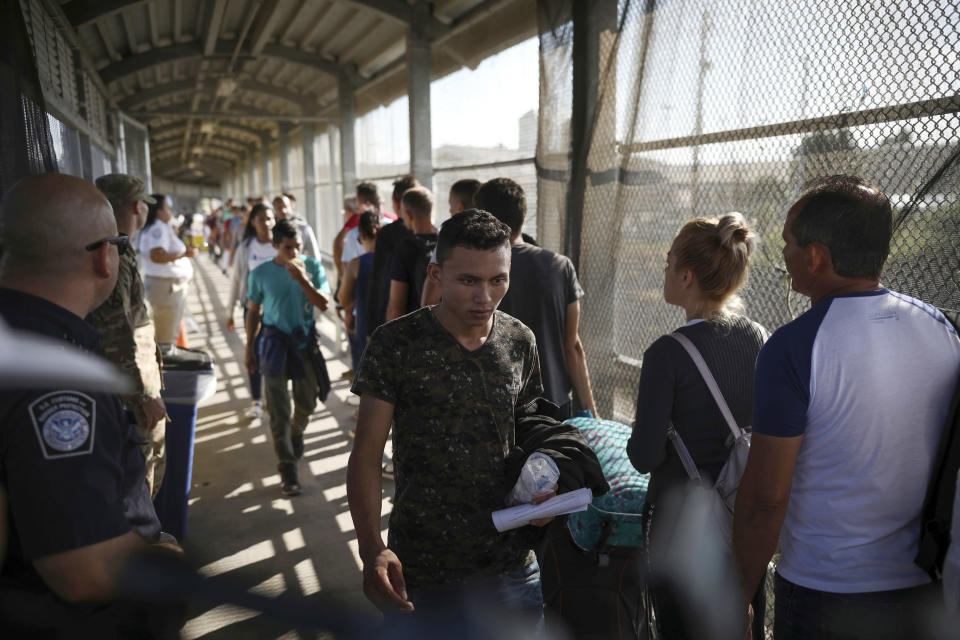 FILE - In this Aug. 2, 2019 file photo, migrants return to Mexico as other migrants line up on their way to request asylum in the U.S., at the foot of the Puerta Mexico bridge in Matamoros, Mexico, that crosses into Brownsville, Texas. Some asylum seekers were told by officials Friday, March 5, 2021, that the U.S. government may reopen their cases and they would eventually be able to enter the U.S. to wait out the asylum process. (AP Photo/Emilio Espejel, File)
